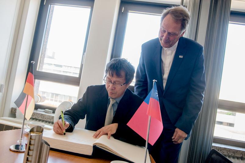 Der Repräsentant Taiwans, Jhy-wey Shieh, trägt sich im Beisein von Rektor Axel Schölmerich ins Gästebuch der RUB ein.