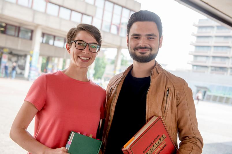 Zwei Studierende stehen nebeneinander mit Büchern in der Hand.