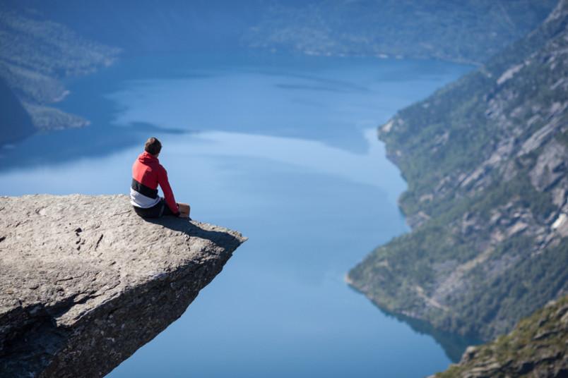 Mann sitzt am Rand einer Felsklippe.