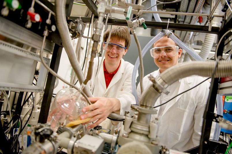 zwei Forscher schauen durch eine Apparatur.