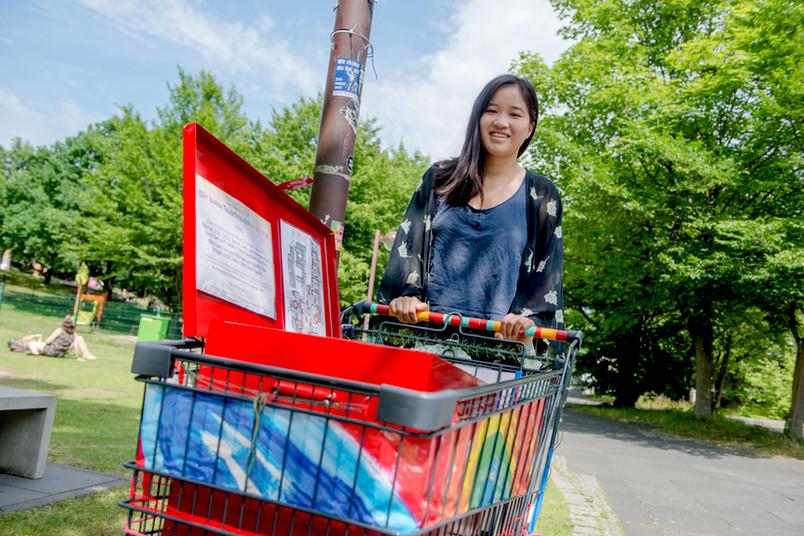 Eine Frau steht hinter einem bunten Einkaufswagen, in dem eine bunte Box steht.