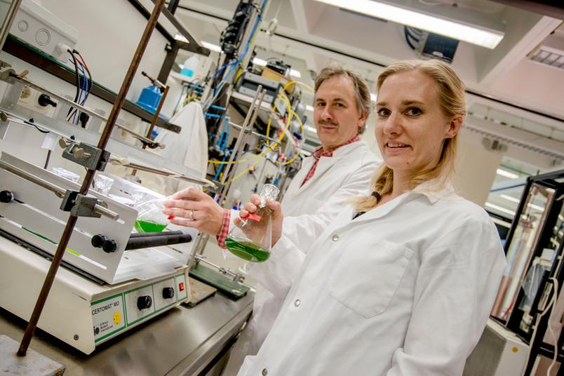Forscher mit grünen Flüssigkeiten in Kolben