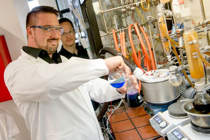Forscher hantieren mit bunten Flüssigkeiten im Labor.