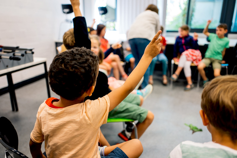 Kinder sitzen im Stuhlkreis und zeigen auf