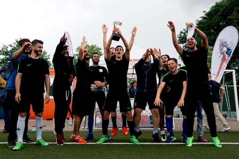 Jubelnde Fußballmannschaft mit Pokal