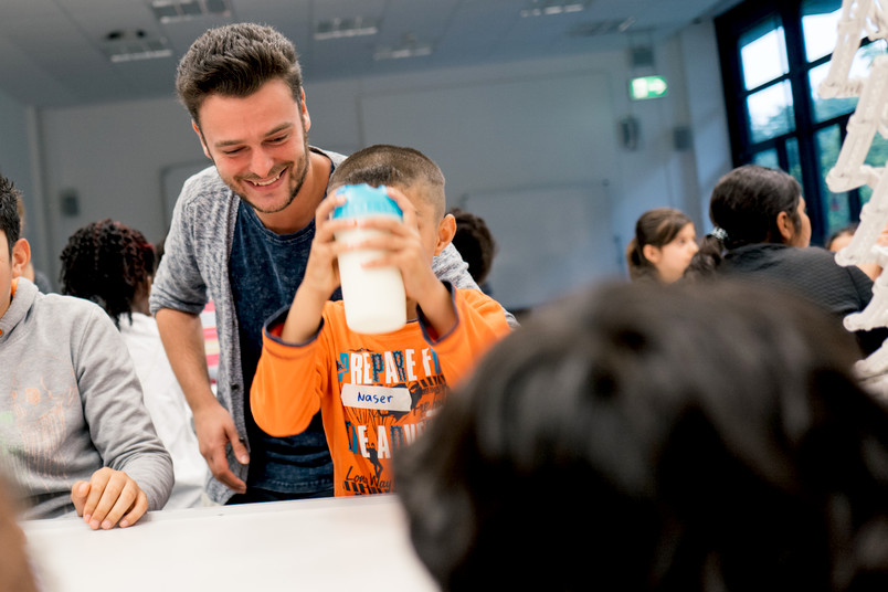 <div> Student Marco Lucas erforscht mit den Schülern die Eigenschaften der Milch.</div>