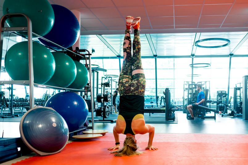 Eine Frau macht in einem Fitnessstudio einen Kopfstand