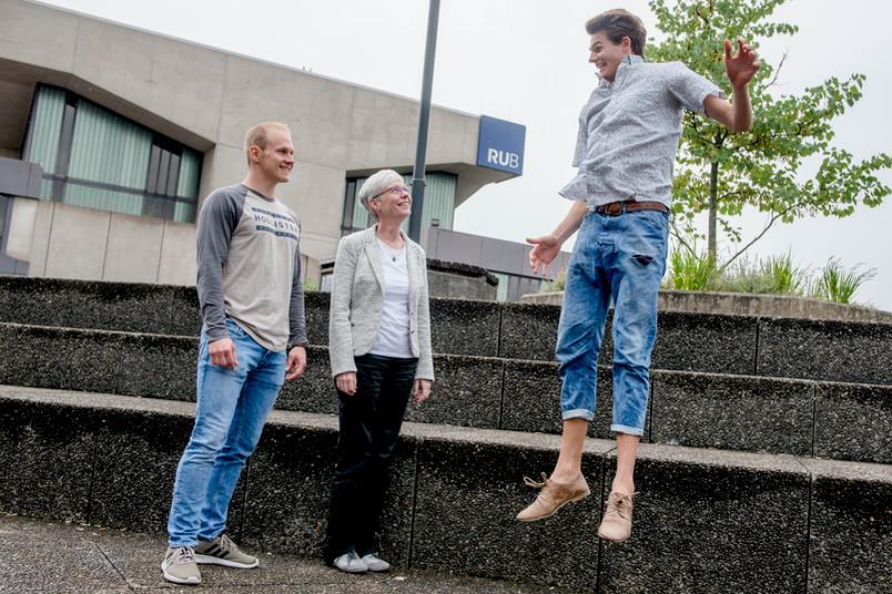 Eine Frau und ein Mann schauen einem Mann beim Springen zu.