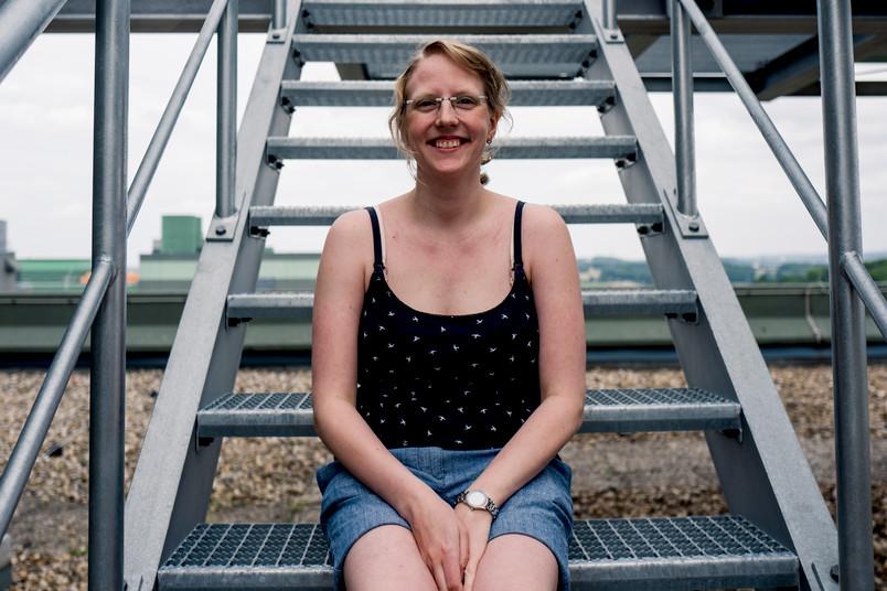 Junge Frau sitzt auf einer Treppe auf einem Dach.