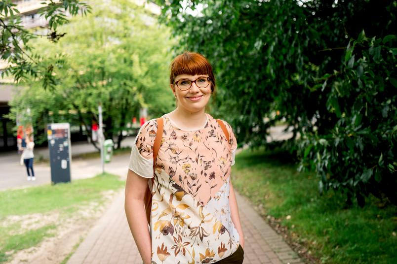 Studentin steht an einer Wiese.