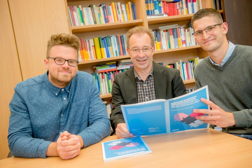 Drei Männer halten eine gedruckte Publikation in den Händen.