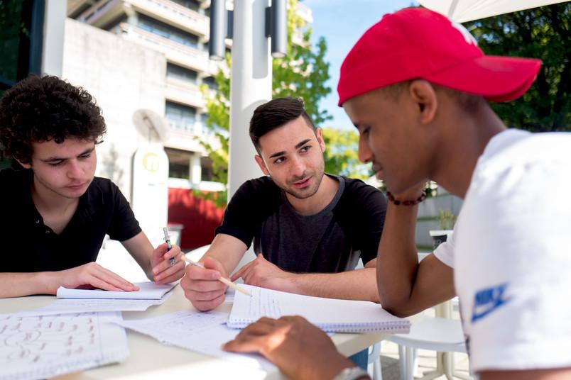 Zwei Schüler lernen mit einem Lehrer.