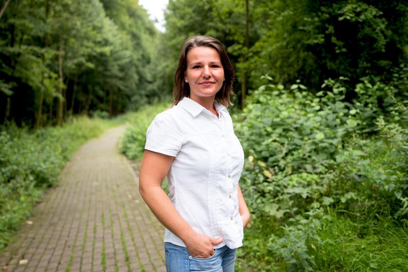 Eine Frau mit weißer Bluse steht zwischen Sträuchern auf einer Wiese.