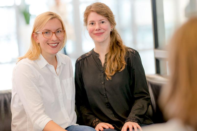Zwei junge Frauen sitzen auf einem Sofa.