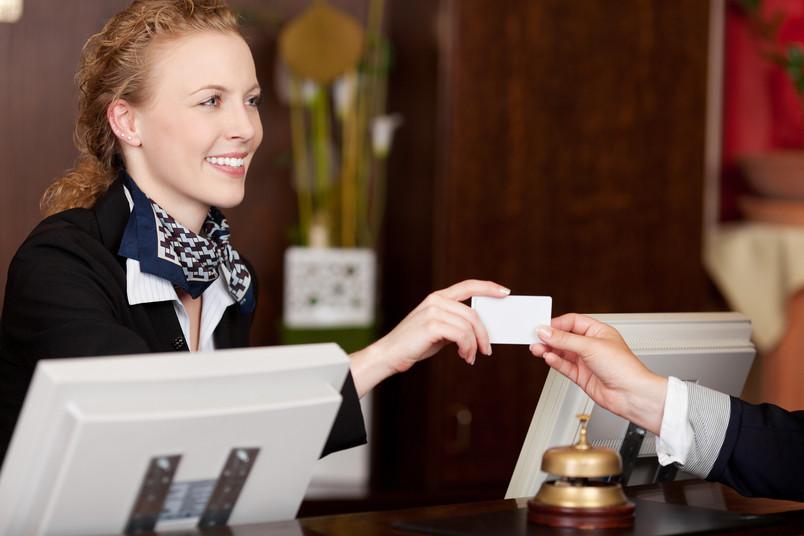 Frau an Hotelrezeption reicht jemandem einen Zimmerschlüssel.