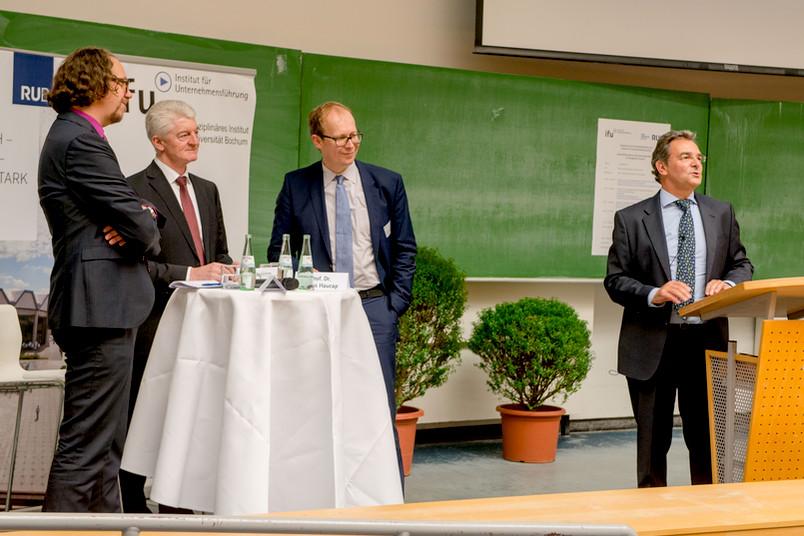 Joachim Gassen, Heinrich Hiesinger, Justus Haucap und Bernhard Pellens bei der Podiumsdiskussion im Hörsaal.