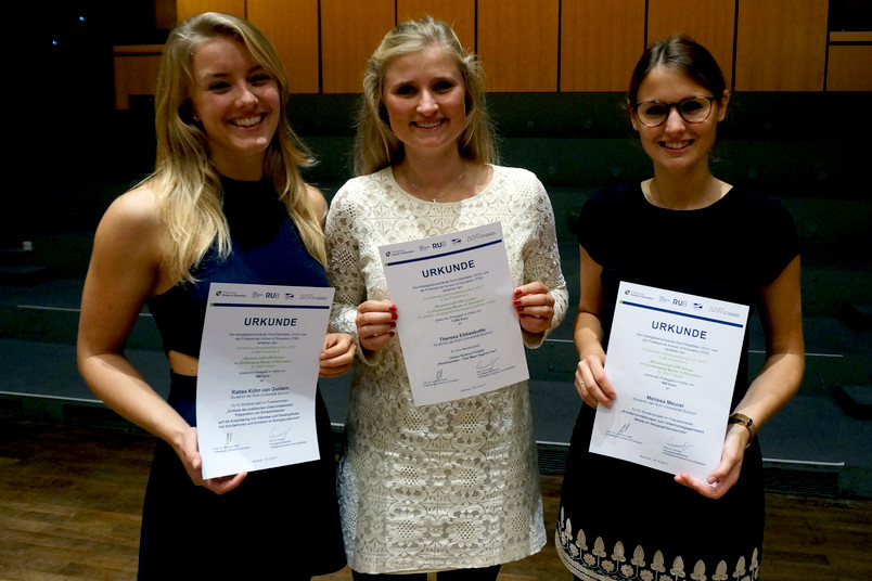 Drei Studentinnen mit Urkunden