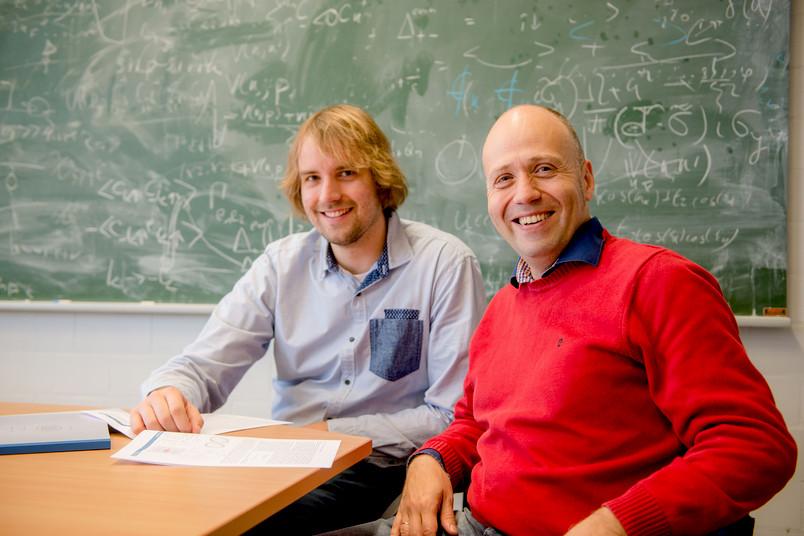 Zwei Männer vor einer Tafel mit Formeln