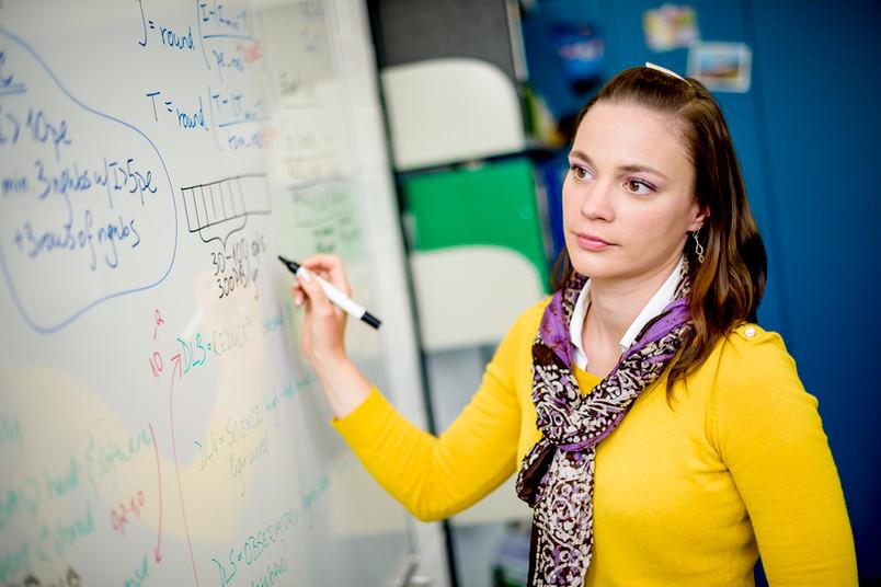 Frau schreibt Formeln an ein Whiteboard.