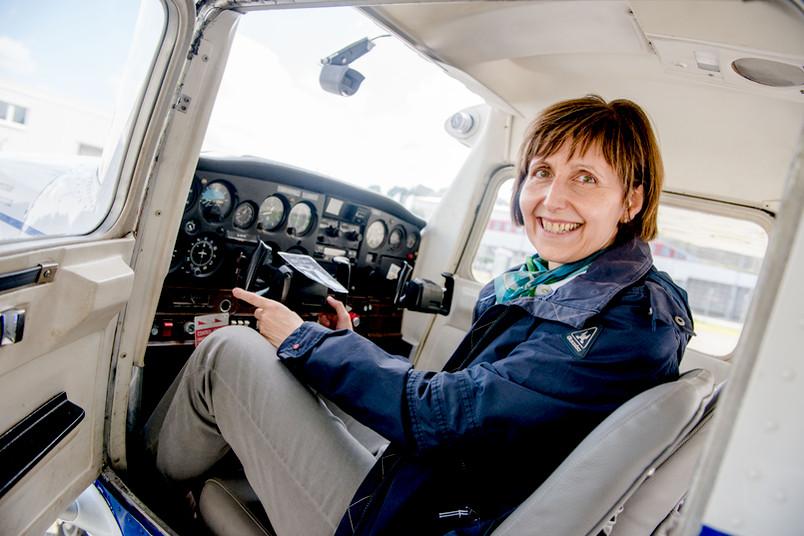 Frau sitzt im Cockpit eines Flugzeuges.