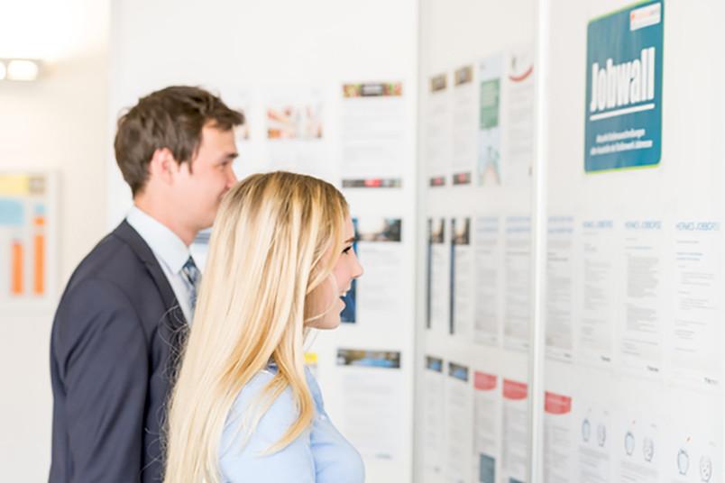 Zwei junge Menschen schauen sich eine Anzeigenwand an.