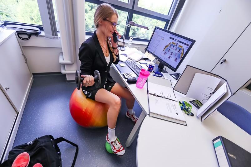 Frau am Schreibtisch macht bei der Arbeit Sportübungen.