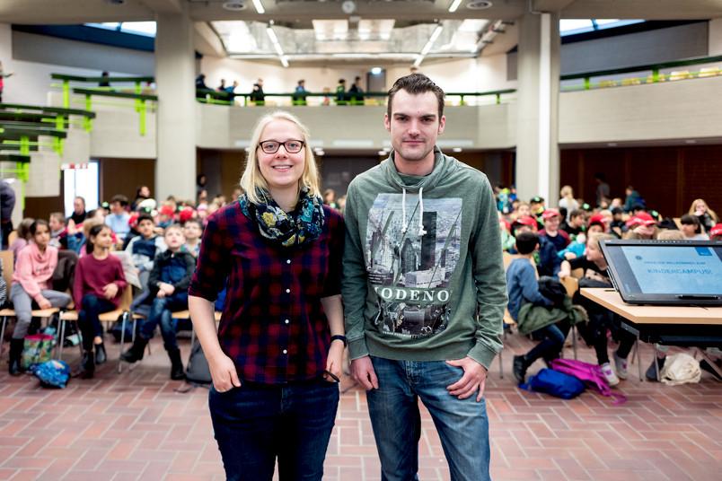 Eine Studentin und ein Student stehen mit dem Rücken zu einem Auditorium, das aus mehreren hundert Kindern besteht