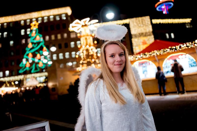 Eine blonde Frau steht im Engelskostüm auf dem Weihnachtsmarkt.
