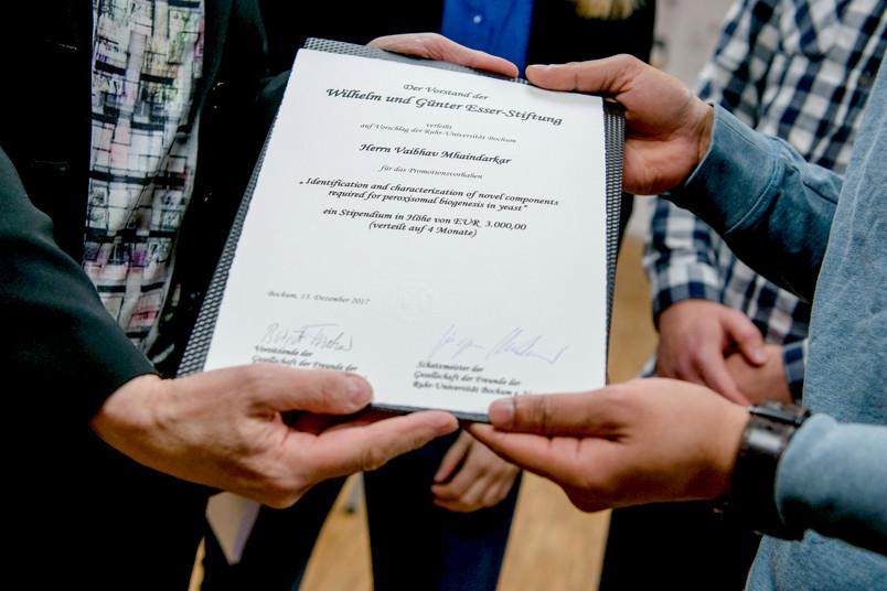 Viele Hände halten eine Urkunde