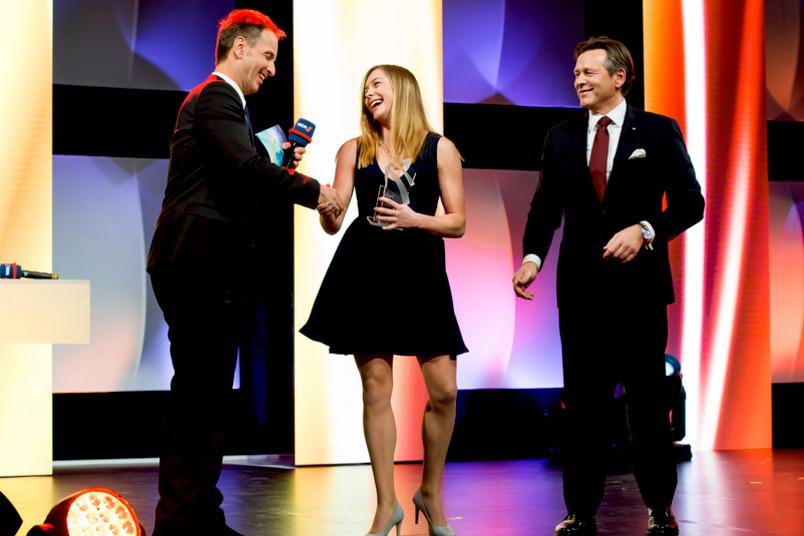 Zwei Männer im Anzug und eine Frau im Kleid stehen lachend auf einer Bühne