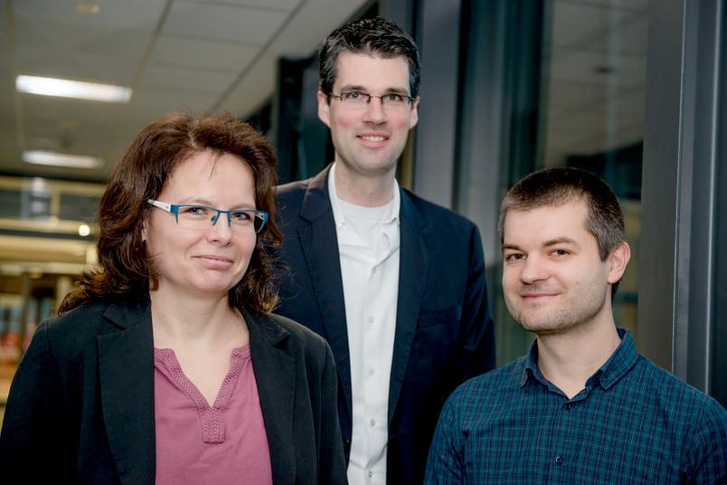 Eine Frau und zwei Männer blicken in die Kamera