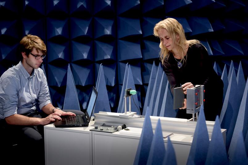 Zwei Forscher in einem dunklen Raum mit Zacken an den Wänden.