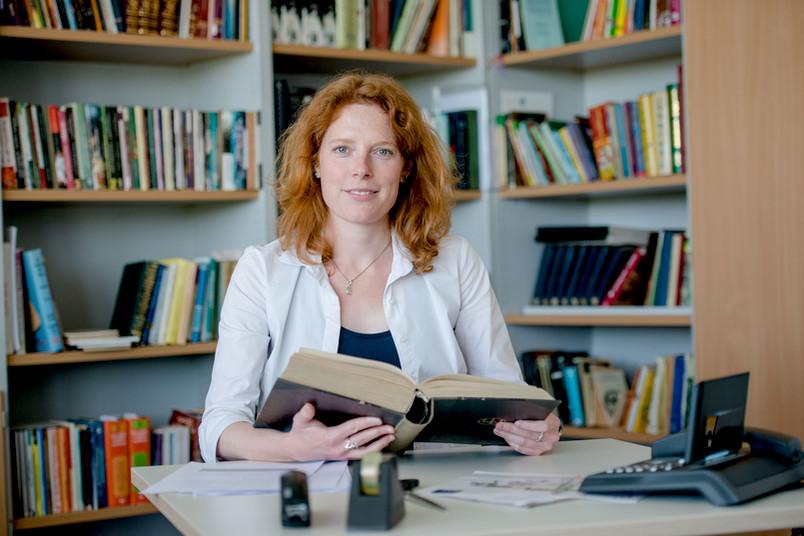 Forscherin mit dickem Buch in der Hand