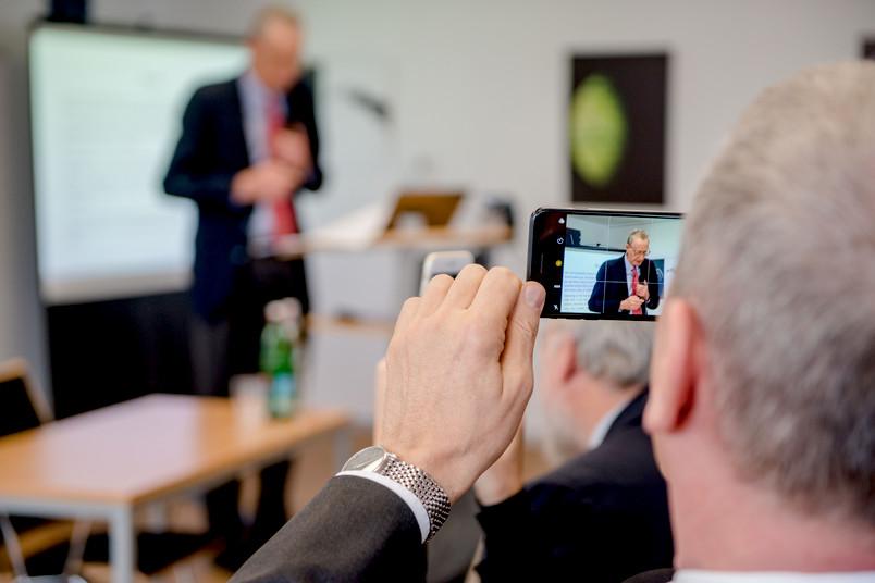 Mann hält Rede, anderer Mann filmt mit Smartphone