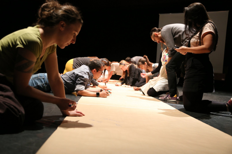 Studierende bemalen einen Papierbogen.