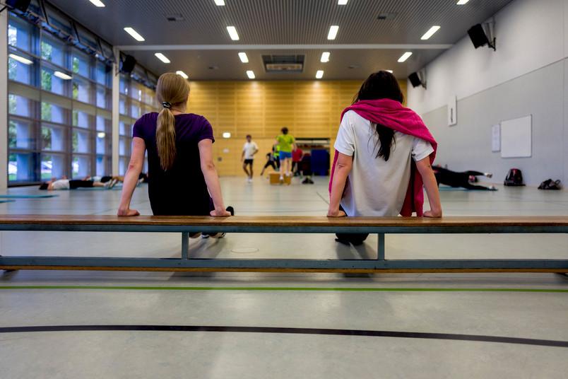 Zwei Frauen stützen sich in einer Sporthalle mit den Amren auf einer Bank ab.