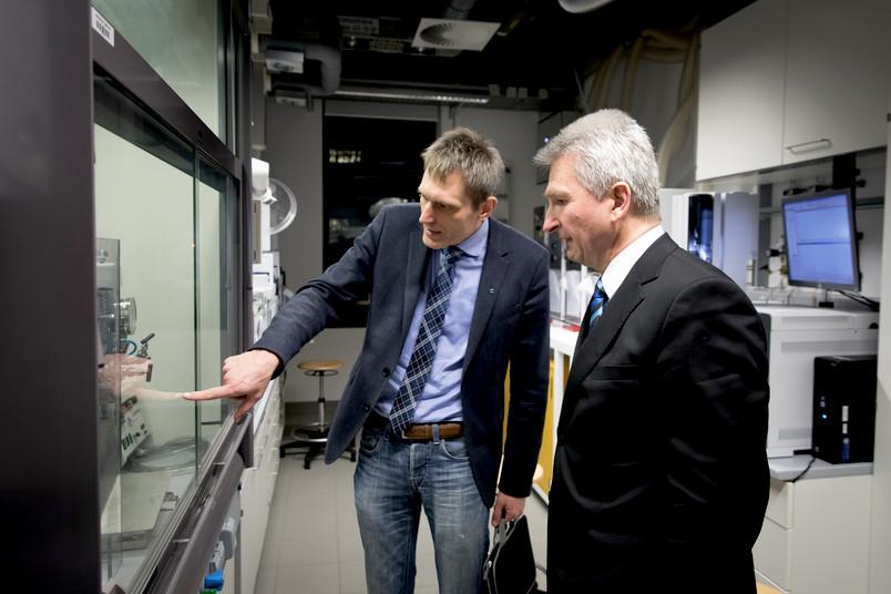 Lukas Gooßen erläutert dem NRW-Wirtschaftsminister Andreas Pinkwart ein chemisches Experiment hinter Glas