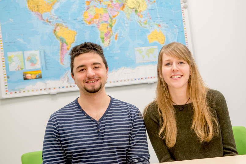 Ein Student und eine Studentin sitzen vor einer Weltkarte.