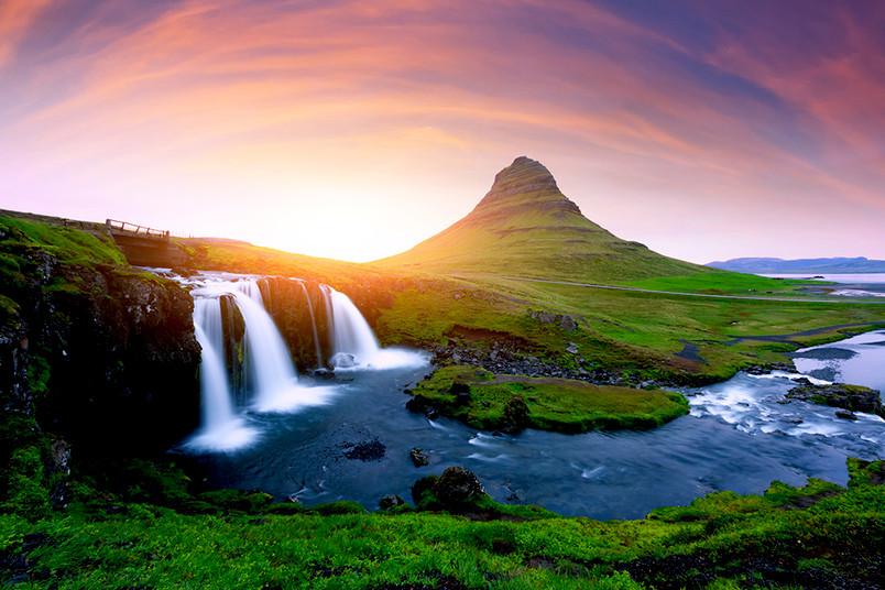 <div> Im Vordergund der isländische Wasserfall Kirkjufellsfoss, im Hntergrund der Vulkan Kirkjufell</div>