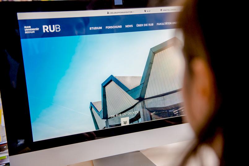 Frau am Computerbildschirm sieht das neue Webdesign der RUB