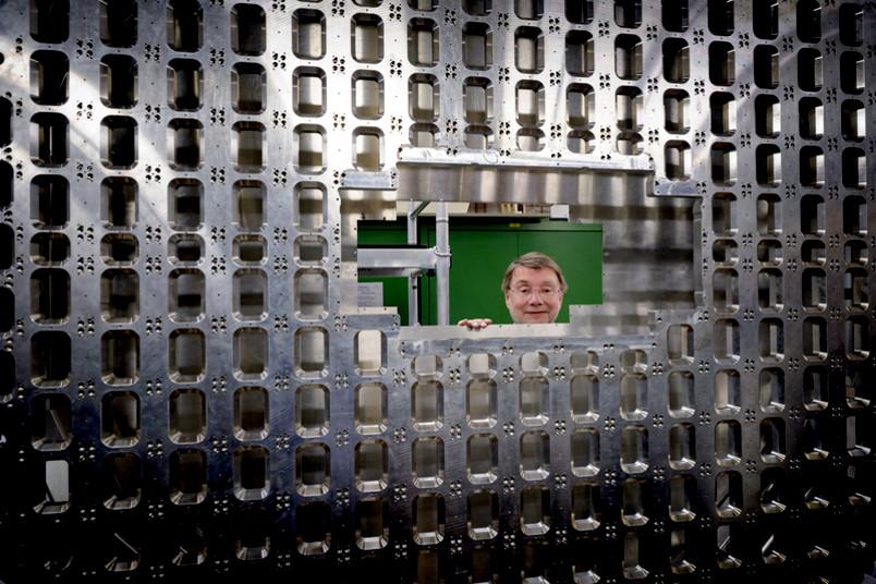 Ein Mann schaut durch eine große Metallkonstruktion.