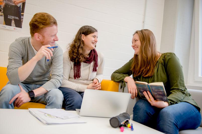 Drei Studierende sprechen miteinander.