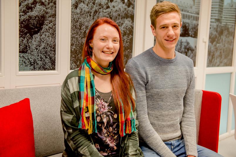 Zwei Studierende sitzen auf einem Sofa.