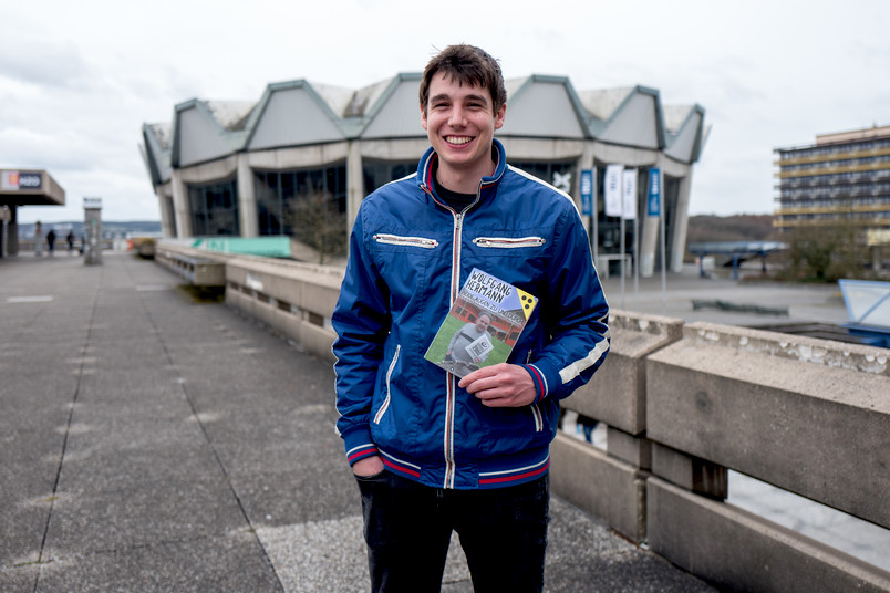 Student hält ein Buch in der Hand.