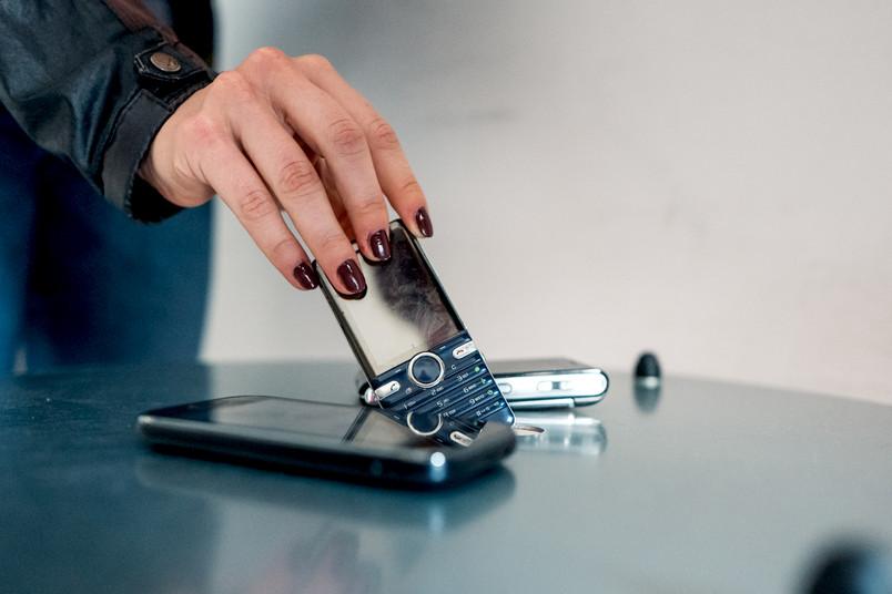 Eine Hand wirft ein altes Handy in einen Schlitz in einer Box.