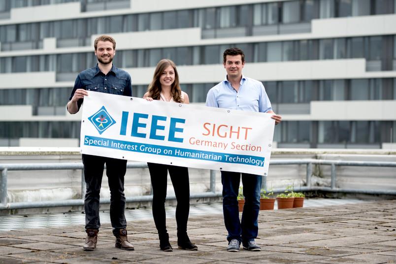 Drei Personen präsentieren ein Banner