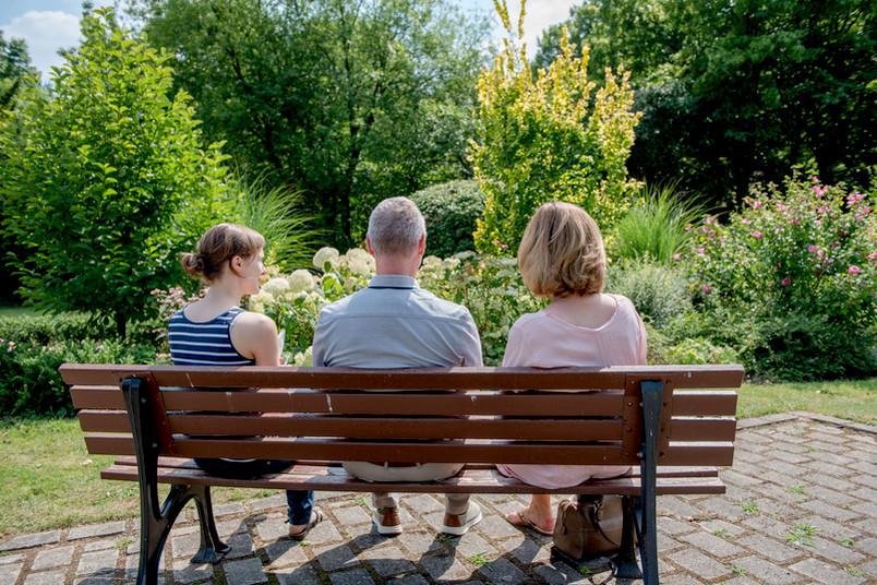 Drei Leute machen Pause auf einer Bank.