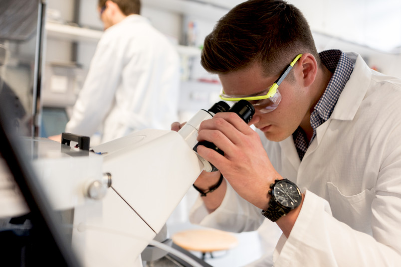 Kevin Wonner schaut durch ein Mikroskop.