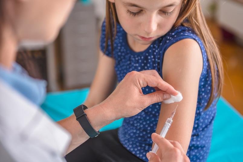 Ein junges Mädchen bekommt eine Spritze in den Arm.