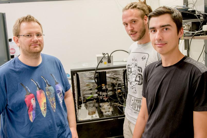 Drei Forscher vor einer Messkammer